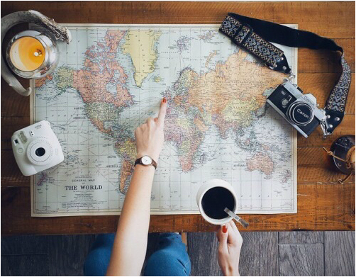 Travel planning on a desk covered with a world map